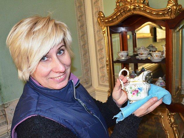 Andrea Minaříková utírá prach z porcelánu v nově vyzdobeném pokoji.