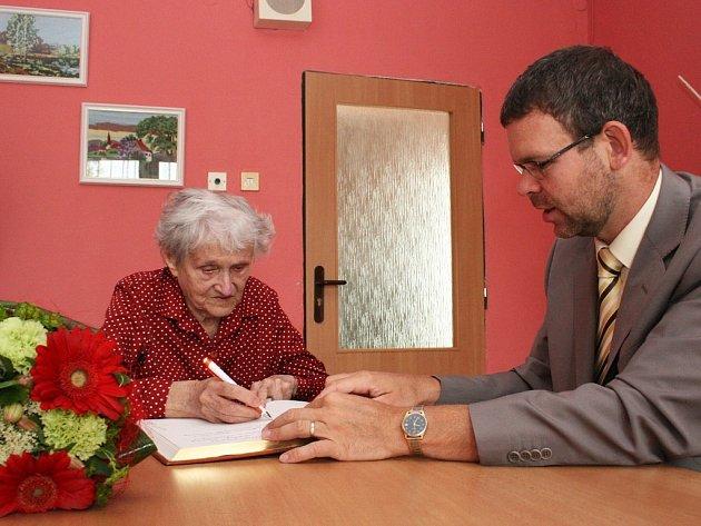 Marta Štanclová se za asistence lounského starosty Jana Kernera podepisuje do pamětní knihy města.