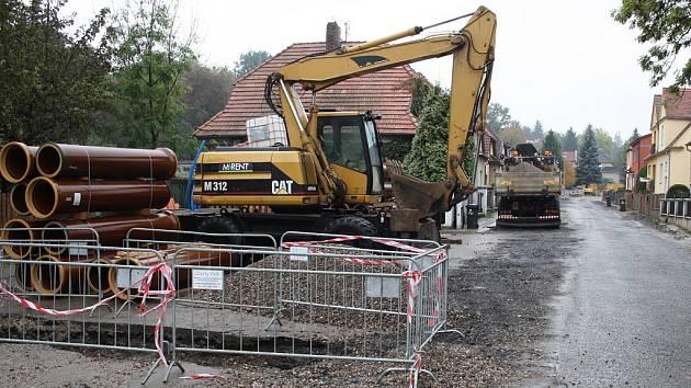 Pracovní stroje v Lučanské ulici. Kvůli zdržení prací na rekonstrukci kanalizace a vodovodu se nové  povrchy chodníků a vozovky budou pokládat až na jaře.