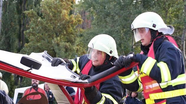 Hasiči Pavel Fůs a Josef Kulich (zleva) odstraňují střechu havarovaného auta pro lepší a bezpečnější manipulaci se zraněnou osobou.