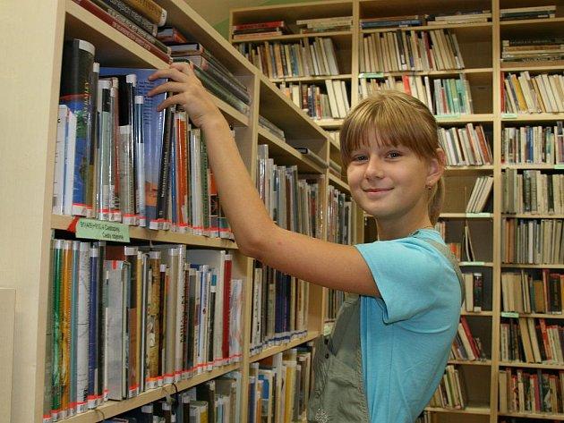 Markéta Malá si prohlíží knížky v nově otevřené knihovně v Lounech krátce po zahájení provozu v srpnu 2010.