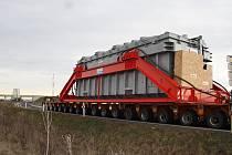 """Jeden z transformátorů pro rozvodnu v Hradci, který se loni v lednu převážel jako nadměrný náklad o váze téměř 450 tun z Lovosic, kam přicestoval lodí z Německa, přes Libčevesko, Postoloprtsko  a Žatecko a """"nocoval"""" u zóny Triangle."""
