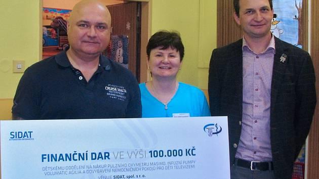 Ředitel nemocnice Jindřich Zetek (vlevo) a primářka dětského oddělení Zdeňka Zasadilová přijímají symbolický šek z rukou jednatele společnosti Radima Novotného.