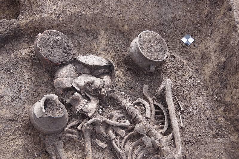 Detail hrobu. Pohřbená pravděpodobně patřila ksociálně výše postaveným, neboť jako milodary jí do hrobu byly vloženy tři keramické nádoby, dvě kostěné tzv. berličkovité jehlice přiložené klevé paži, prasečí kopýtko u nohou, a především náhrdelník zperl