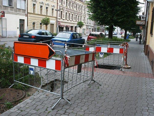 Propadlý chodník v Husově ulici v Lounech.