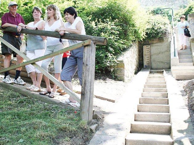 Účastníci křtu si prohlížejí upravené okolí kolem vodoznaku u řeky Ohře v Lounech. Její hladina se dá odečítat z rysek s čísly vyznačenými na kamenných schodech.