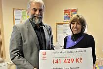 Miroslav Krpec z Postoloprt, ředitel Elektrárny Mělník, předává za firmu ČEZ symbolický šek ředitelce Oblastní charity Ústí nad Labem Michaele Klapkové Ozomové.