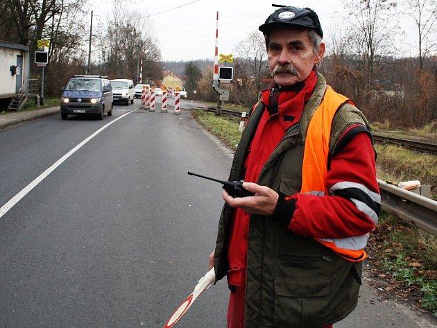 Václav Končelík řídí dopravu poblíž železničního přejezdu v Žiželicích, kde se opravuje silnice Most – Plzeň.