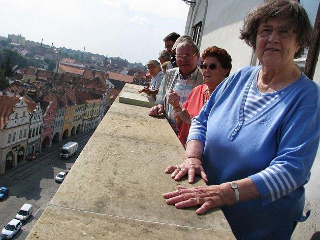 Němečtí turisté shlížejí z ochozu radniční věže na Žatec při návštěvě města.
