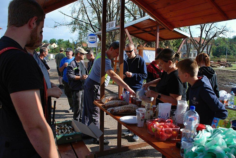 Sobota 3. července v obci Stebno na Lounsku. Místní ženy hostí pomocníky.