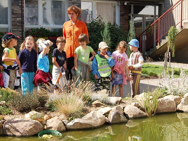 Děti ze školky si prohlížejí botanickou zahradu s jezírkem v Žatci.