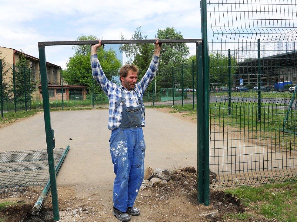 Dělník při opravě poškozeného plotu a vstupní branky