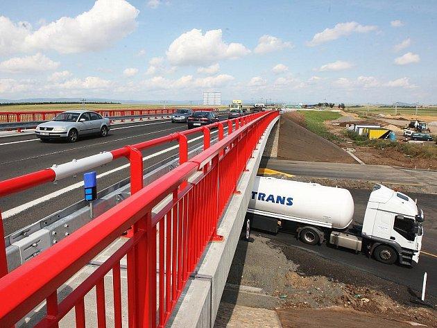 Auta jedou po novém mostě na silnici Žatec – Most, dole je silnice na Prahu.