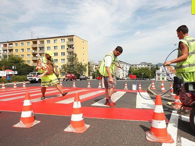 Dělníci nanášejí speciální reflexní červenou barvu na jeden z nejfrekventovanějších přechodů pro chodce v centru Loun.