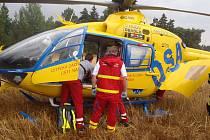 Záchranáři nakládají zraněného mladého muže do vrtulníku.