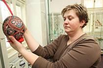 Kurátorka výstavy s názvem Jaro přišlo k nám Jitka Krouzová ukazuje kraslice v Regionálním muzeu K. A. Polánka v Žatci.