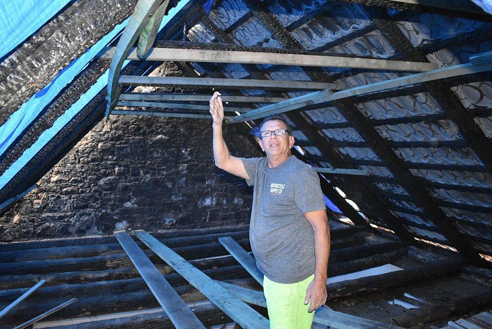 Míla Přibylů ukazuje, jak požár poničil střechu domu.