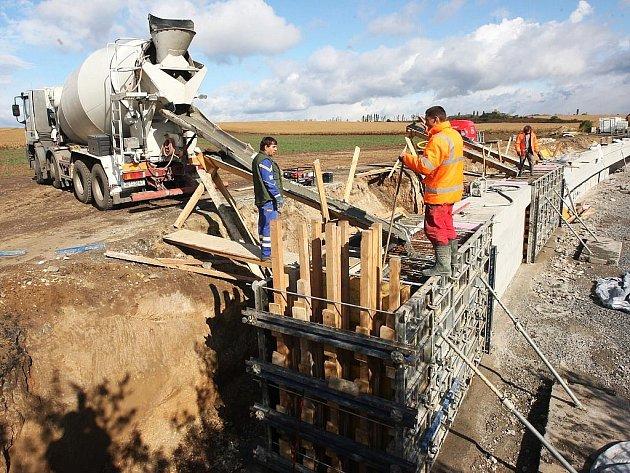 Dělníci staví opěrné zdi na silnici u Staňkovic