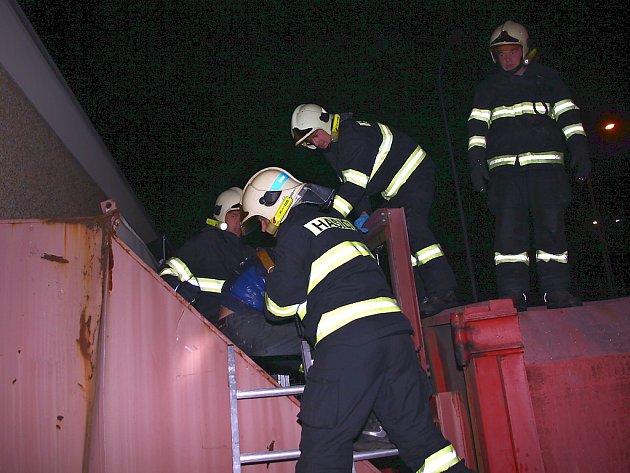Hasiči pomáhají muži z kontejneru.