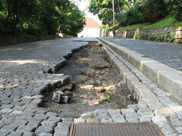 Díra v ulici Pod Střelnicí v Žatci. Proud vody tam na několika místech odnesl dlažební kostky