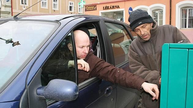 Miroslav Kryštůfek z Technické správy města Loun vysvětluje řidiči, jak správně vytáhnout parkovací lístek z automatu.