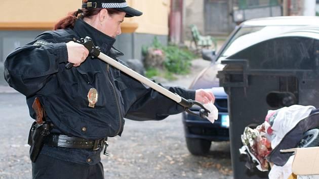Pomocí tyče s úchopným zařízením zkoumá žatecká strážnice Simona Petriková,  kdo  volně odhodil  vedle kontejneru odpad.