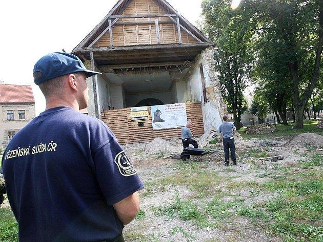 Odsouzení muži pracují u lenešického kostela. Při práci je hlídá vězeňská služba.