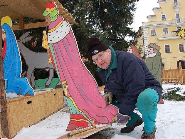 Jiří Kvapil skládá dřevěné barevné figury, součásti betlému, který tradičně v době adventu a Vánoc zdobí náměstí v Žatci.
