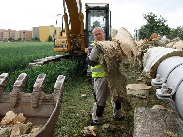 Dělníci rozebírají potrubí podél silnice Žatec – Holedeč na jižním okraji města.