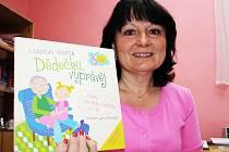 Alena Šubrtová, ředitelka pořádající školky, s knížkou pro děti, kterou dostanou účastníci festivalu