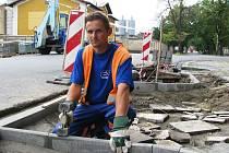 Václav Koželuh pokládá obrubník chodníku na nově budovaném přechodu pro chodce v Rooseveltově ulici v Žatci.