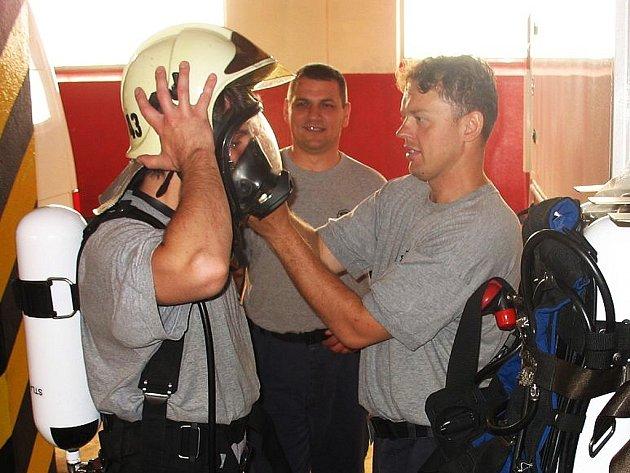 Profesionální hasiči z Elektrárny Počerady Petr Podhajský (v masce) a Jindřich Martínek zkoušejí  dýchací techniku. Přihlíží zástupce velitele stanice Václav Helšus.