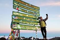 Lubomír Peterka u známé cedule na vrcholu Uhuru, nejvyššího bodu masivu Kilimandžáro a zároveň celé Afriky