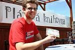 Ondřej Kunc z lounské knihovny láká na archivním snímku do plážové knihovny na místním koupališti.