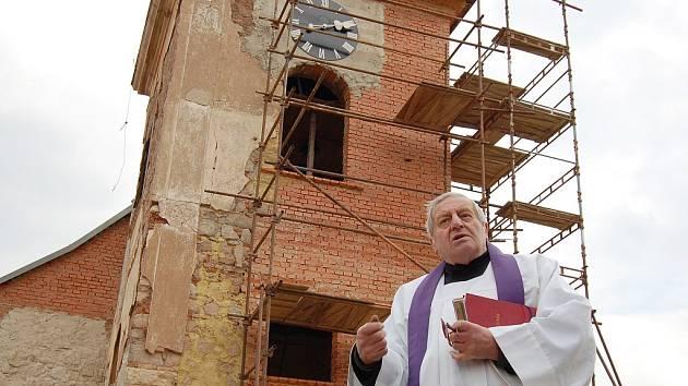 Páter Josef Šimon, administrátor římskokatolické církve v Kryrech, symbolicky žehná zvonům ve věži kostela ve Vidhosticích.