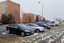 Zaparkovaná auta na okraji pole v žatecké ulici Stavbařů. V budoucnu by v místě mělo vzniknout parkoviště.