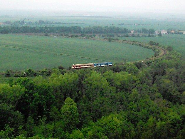 Rychlík na trati mezi Plzní a Mostem projíždí pod vrchem Rubín  nedaleko Podbořan.