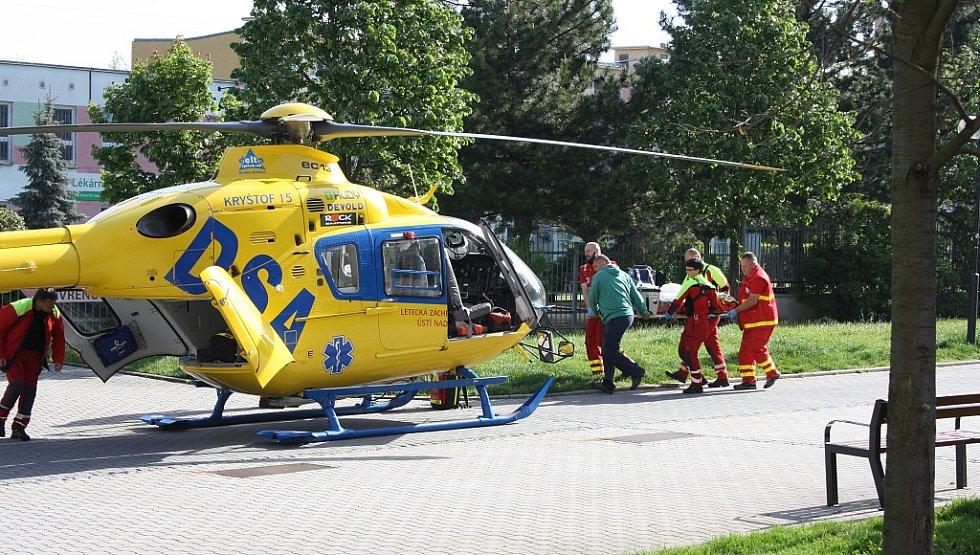 Záchranáři nakládají zraněnou ženu do vrtulníku