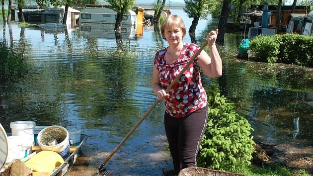 Vedoucí kempu U Hráze Lenka Jirkovská uklízí naplaveniny, které přinesla velká voda