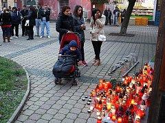 Lidé před pizzérií zapalují svíčky.