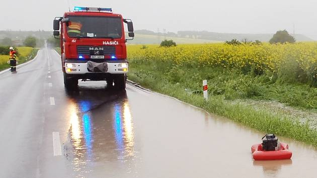 Hasiči odčerpávají vodní lagunu ze silnice u Sýrovic