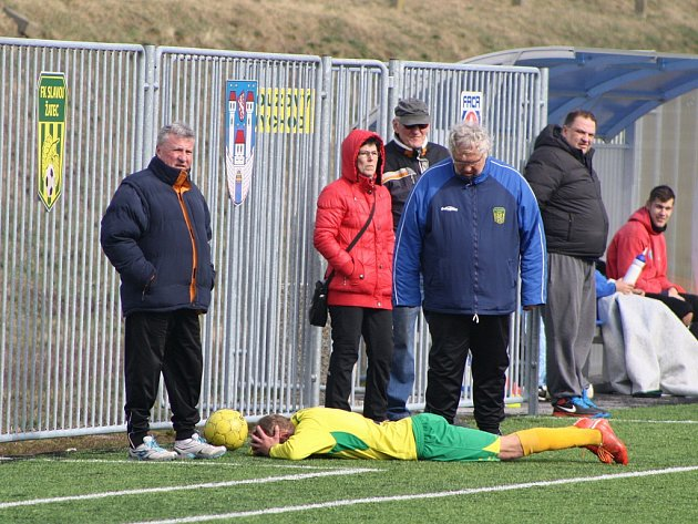 Utkání Žatce (ve žlutém) proti Lovosicím. Zraněný Petr Klinec s bolestivou grimasou leží v prostoru u střídaček.