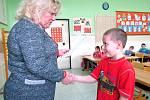 Dvojčata při přebírání prvního vysvědčení v žatecké škole. Na snímku učitelka Jana Piwková s Jeníkem.