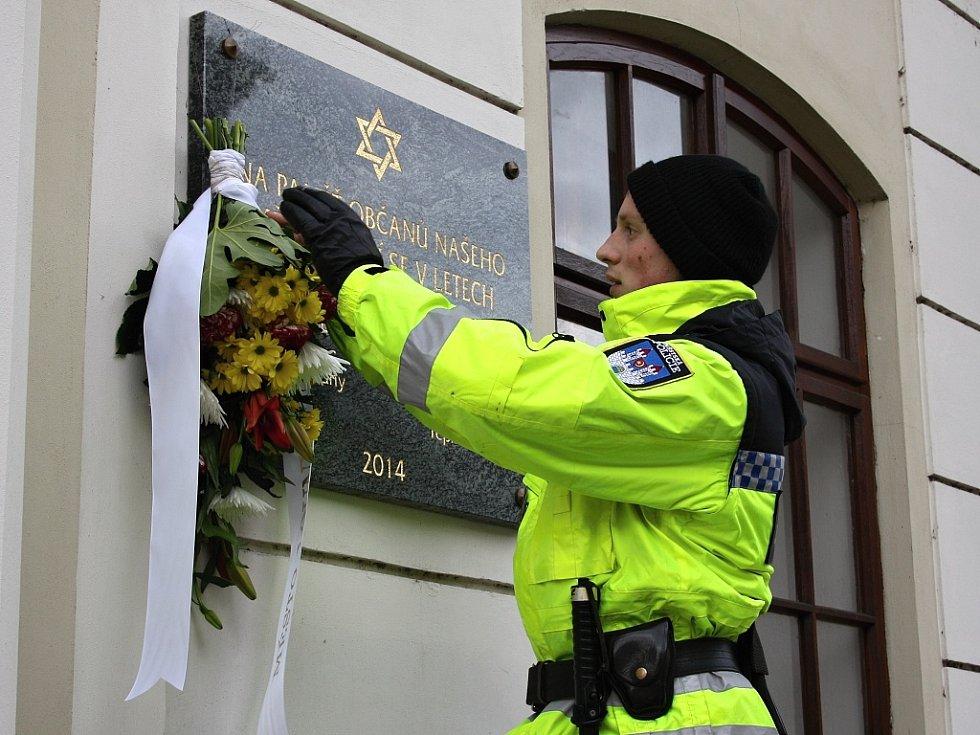 Strážník upevňuje květinu na pamětní desku na lounské synagoze