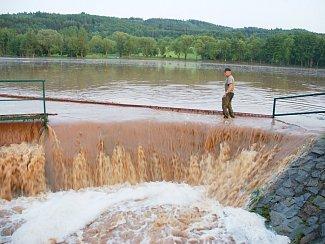 Voda valící se přes hráz lubeneckého rybníka při velké povodni  loni v červnu.