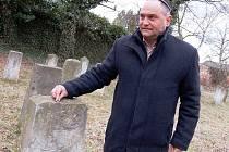 Předseda Židovské obce Teplice Oldřich Látal pokládá podle starého židovského zvyku kamínek na jeden ze zbylých náhrobků na žateckém židovském hřbitově.