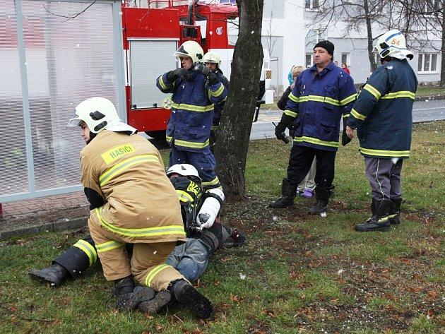 Hasiči drží muže, který jim bránil v práci při požáru v Počeradech. Později pro něj přijela policie.
