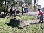 Pracovníci Technické správy města Žatec uklízejí okolí podstavce pomníku v parčíku u žateckého západního vlakového nádraží