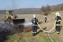 Hasiči likvidují požár hromady listí a větví na okraji Žatce, rozebíral ji majitel pole s nakladačem.
