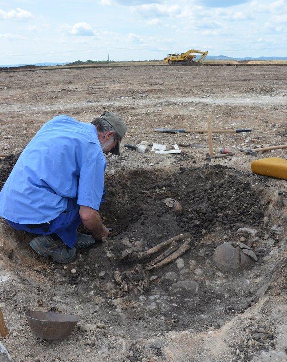 Brigádník J. Poláček odkrývá hrob z pozdní doby kamenné.